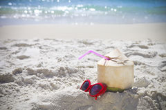 Fresh coconut cocktail and red sunglasses on the beach. Fresh coconut cocktail and red sunglasses on tropical beach Royalty Free Stock Image