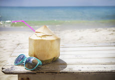 Fresh coconut cocktail and sunglasses on tropical beach. Fresh coconut cocktail and blue sunglasses on tropical beach Stock Image