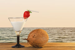 Fresh coconut cocktail on a tropical beach during sunset. Fresh coconut cocktail with strawberries on a tropical beach during sunset on a wooden table - a Stock Photo