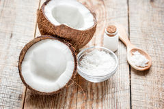 Fresh coconut with cosmetic oil in jar on wooden background. Fresh coconut with organic cosmetic oil in glass jar on wooden background Royalty Free Stock Images