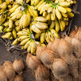 Fresh coconuts and bananas at market place Stock Images
