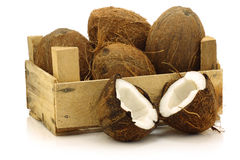Fresh coconuts and a cut one in a wooden crate stock photos