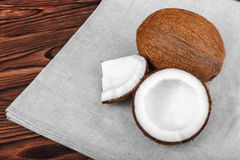 Fresh coconuts and gray cloth on a brown background. Tasty cut coconut on a table. Delicious organic nut cut in pieces. Close-up tasteful coconuts on a dark Stock Image