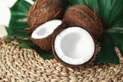 Fresh coconuts with leaf. On wicker mat Royalty Free Stock Image