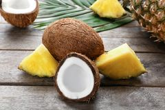 Fresh coconuts and pineapple slices. On wooden background Stock Photos