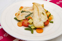 A fresh cod on bed of mixed vegetables Stock Photo