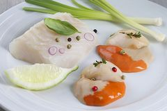 Fresh cod filet. Ready to cook fresh cod filet and scallops with leeks in a plate Royalty Free Stock Photo