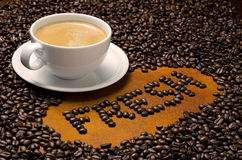 Fresh Coffee. A fresh brewed cup of hot coffee against a background of roasted coffee beans Stock Photography