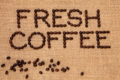 Fresh Coffee. Bean sign in letter word form with loose beans on a hessian background Royalty Free Stock Photo