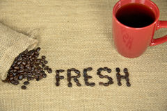 Fresh coffee beans on burlap with mug Royalty Free Stock Photography