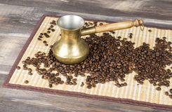 Fresh coffee beans and gold coffee pot on wood table and bamboo cloth Royalty Free Stock Photos