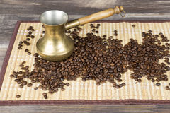 Fresh coffee beans and gold coffee pot on wood table and bamboo cloth Stock Image