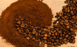 Fresh coffee beans and ground coffee mixed on wooden texture close-up. Stock Photography