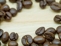 Fresh Coffee beans  on Light wood floor.  Royalty Free Stock Photography