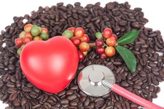 Fresh coffee beans with red heard sign and stethoscope on dry co. Ffee beans background Stock Image