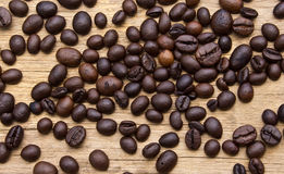 Fresh coffee beans on wood Royalty Free Stock Photos