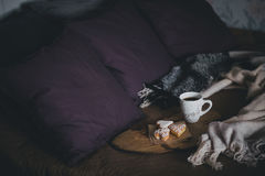 Fresh coffee and biscuits on a wooden tray standing on the bed Stock Images