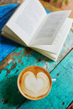Fresh coffee and book on a wooden table Royalty Free Stock Images