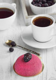 Fresh coffee for breakfast with a cake of marzipan and blackberr. Mousse cake with berries and two cups of coffee at breakfast Royalty Free Stock Image