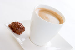 A fresh coffee and chocolate. A cup of creamy black coffee on a square saucer with a chocolate, focussed on the coffee cup Stock Images
