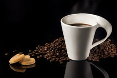 Fresh Coffee. A cup of fresh ground coffee with coffee beans in the back and two cookies to go with it royalty free stock photos