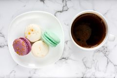 Fresh Coffee cup and plate with colorful macarons on marble table background. Delicious coffee break stock photo