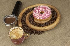 Fresh coffee and a donut. Sweet treats to hot coffee. Traditional dessert Stock Image
