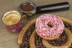 Fresh coffee and a donut. Sweet treats to hot coffee. Traditional dessert Royalty Free Stock Image