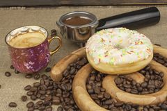 Fresh coffee and a donut. Sweet treats to hot coffee. Traditional dessert Royalty Free Stock Images