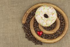 Fresh coffee and a donut. Sweet treats to hot coffee. Traditional dessert Royalty Free Stock Photography