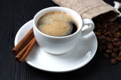Fresh coffee with foam in a white cup with cinnamon and a bag of grains Stock Photography