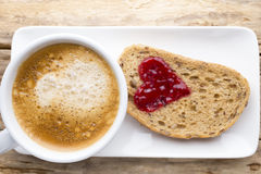 Fresh coffee. Grain slice of bread with jam heart shape. Royalty Free Stock Photo