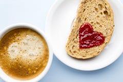 Fresh coffee. Grain slice of bread with jam heart shape. Stock Photography