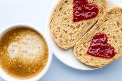 Fresh coffee. Grain slice of bread with jam heart shape. Stock Photo