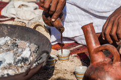 Fresh Coffee. Marsa Alam, Red Sea/ Egypt – OCTOBER 31: unidentified Bedouin young man from Bishari Tribe pouring fresh Bedouin coffee called gabana in a cup Royalty Free Stock Images