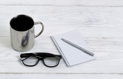 Fresh coffee with reading glasses and writing materials Royalty Free Stock Photos