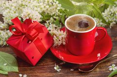 Fresh coffee in red cup and white cherry. Morning coffee for loved ones. Gift in red box and spring flowers royalty free stock photo
