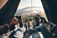 Fresh coffee to continue the adventure. Close up of young couple. Holding mugs while enjoying the view of mountain range from their tent Royalty Free Stock Image