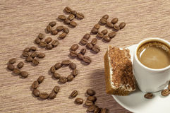 Fresh Coffee Written in coffee Beans. Words fresh coffee written in whole coffee beans with a cup of coffee and cappuccino cake on the side Stock Images