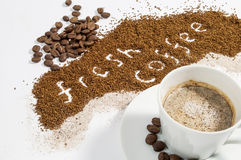 Fresh Coffee Written in Ground Coffee. With whole beans and a cup of cappuccino Royalty Free Stock Photography