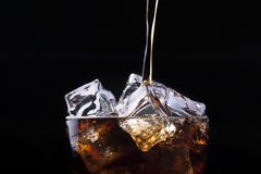 Fresh cola drink background with ice. And splash on a black stock photos