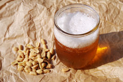 Fresh cold beer in a half liter glass jar and nuts on crumpled paper. Soviet still life with a glass jar of beer Royalty Free Stock Photography