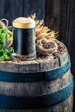 Fresh and cold dark beer on wooden barrel with hops and wheat Royalty Free Stock Photography