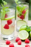 Fresh cold drink water ice cubes peppermint lime raspberry. Outdoor summer Stock Photos