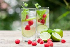 Fresh cold drink water ice cubes peppermint lime raspberry. Outdoor summer Stock Photography