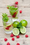 Fresh cold drink water ice cubes peppermint lime raspberry. Outdoor summer Stock Images