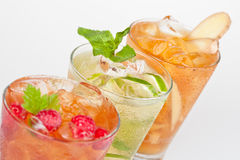 Fresh cold drinks. Three fresh cold drinks with fruit flavour and ice cubes Royalty Free Stock Photo