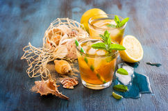 Fresh cold iced tea with mint, ice,  lemons and sea shells, refr Stock Photos
