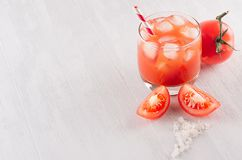 Fresh cold red tomato drink and pulpy tomato with piece, straw, salt on light soft white wood table, copy space, top view. Fresh cold red tomato drink and pulpy Royalty Free Stock Photos