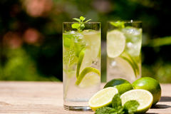 Fresh cold refreshment drink mineral water soda with lime and mint. On wooden table in summer stock photography